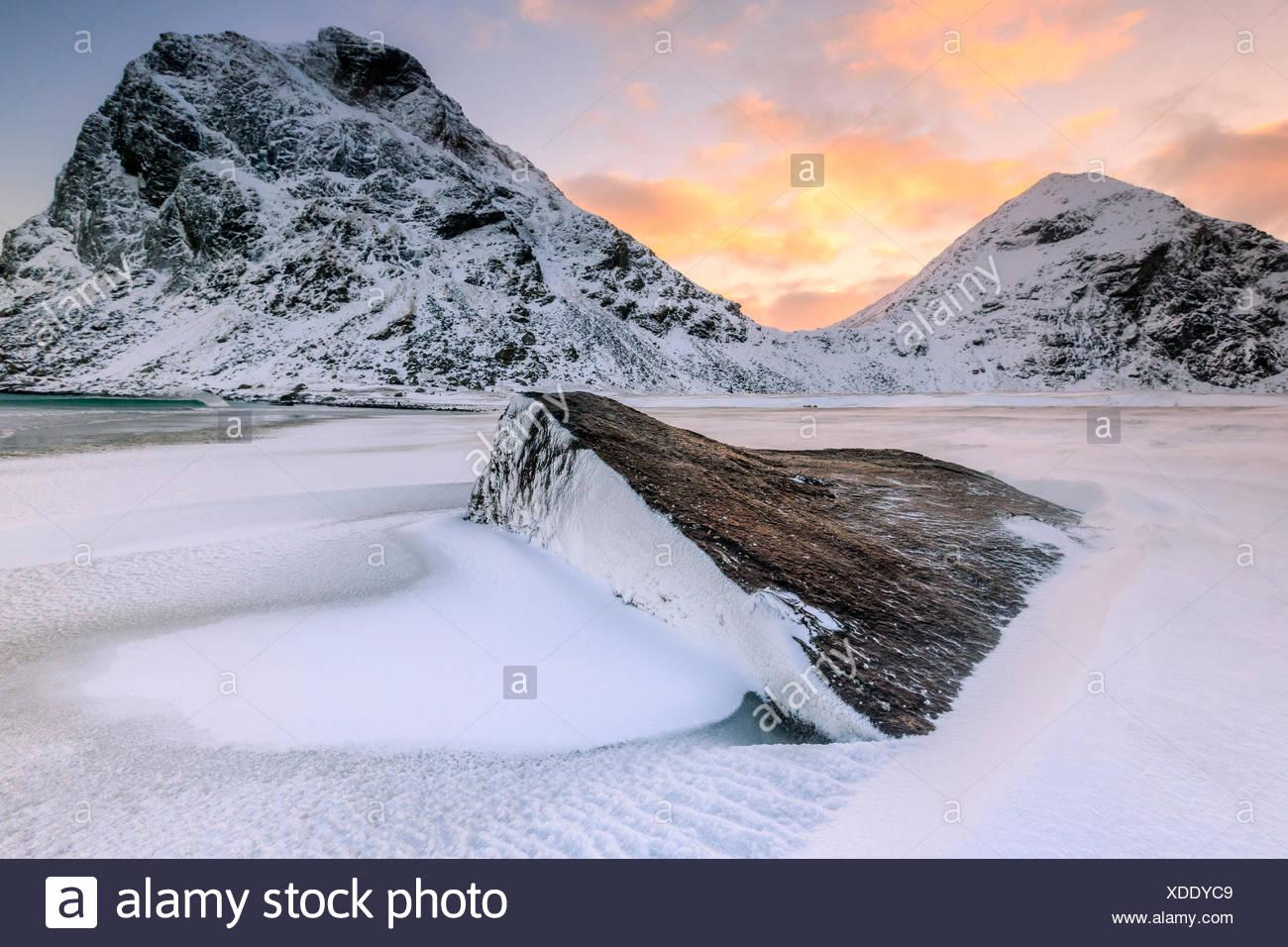 Alba illumina le rocce con la forma dal vento circondata da neve fresca, Uttakleiv Isole Lofoten in Norvegia Europa Immagini Stock