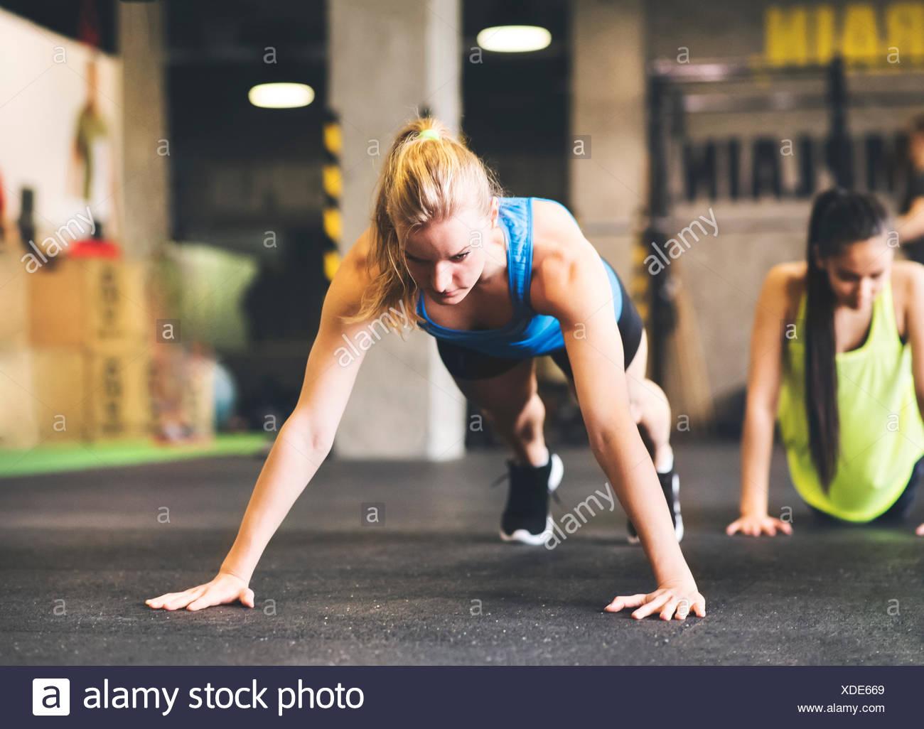 Giovane donna facendo push-up in palestra Foto Stock