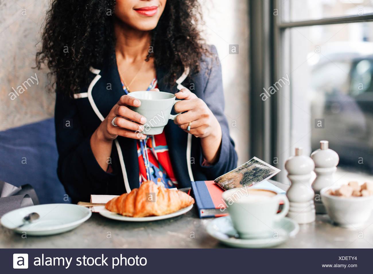 Ritagliato colpo di donna azienda tazza di caffè nella caffetteria Immagini Stock