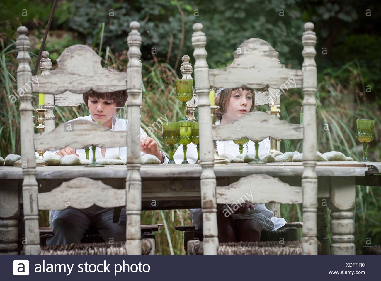I bambini seduti al tavolo da pranzo all'aperto Immagini Stock