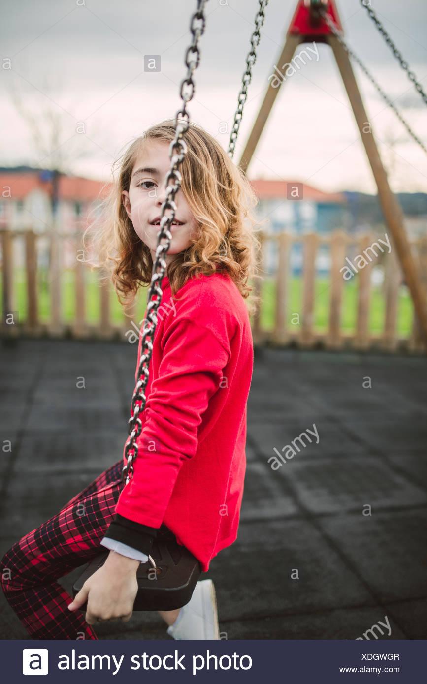 nuovo stile 75c00 bc2ed Bimba bionda che indossa maglione rosso seduto su uno swing ...