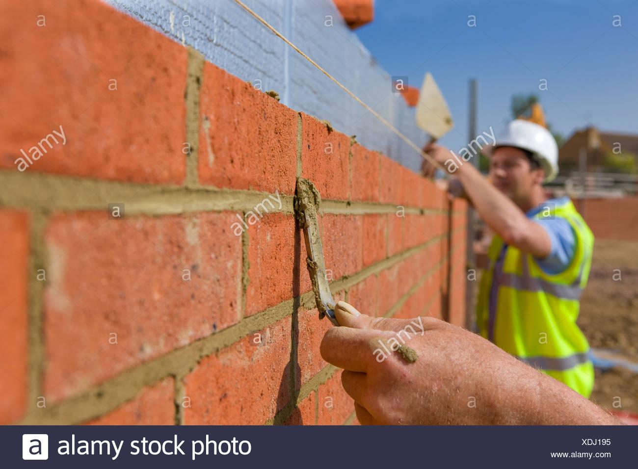 Muratori applicare mortaio di mattoni della parete Immagini Stock