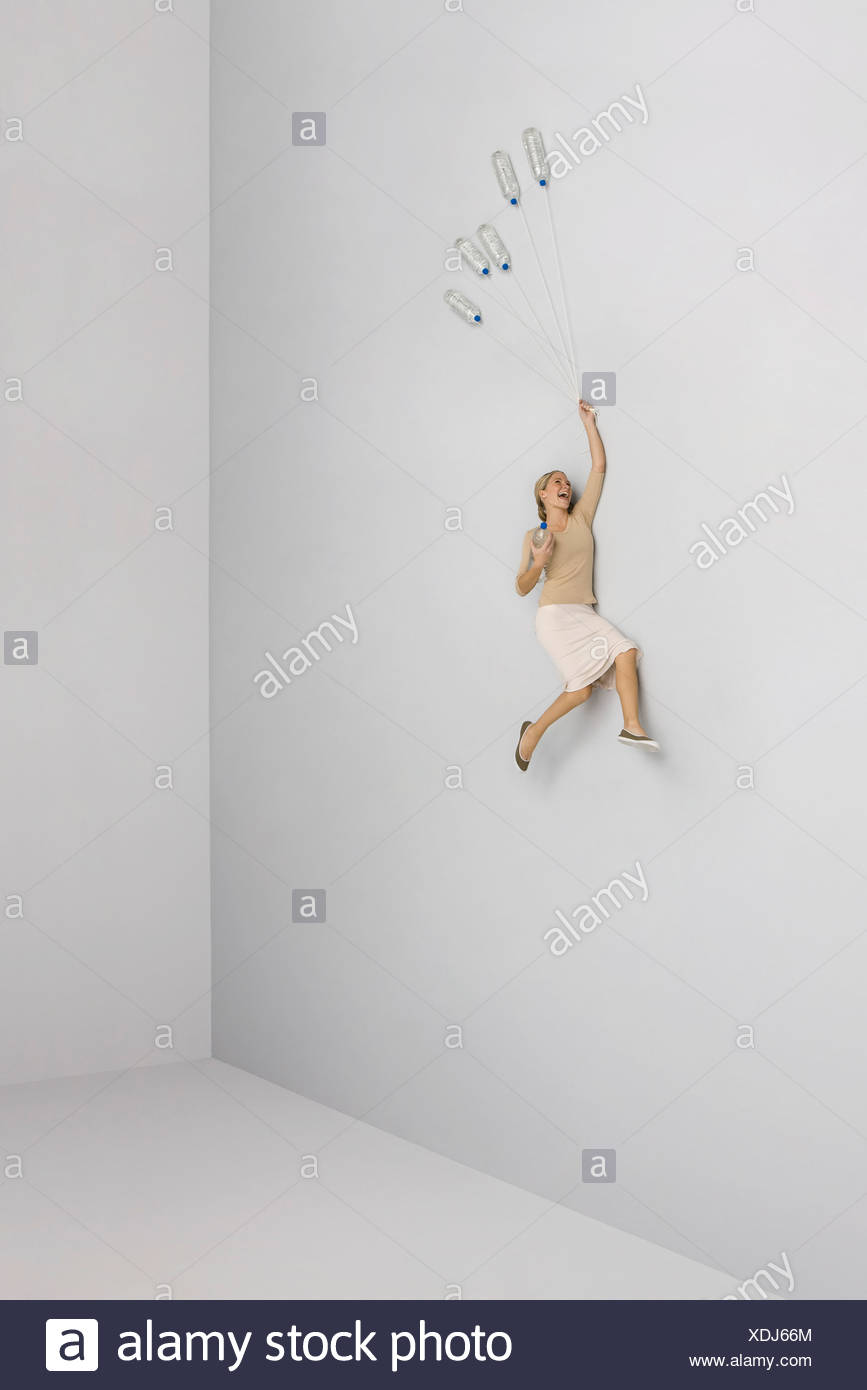 Donna che ride, tenuto aloft dal mucchio di bottiglie di acqua Immagini Stock
