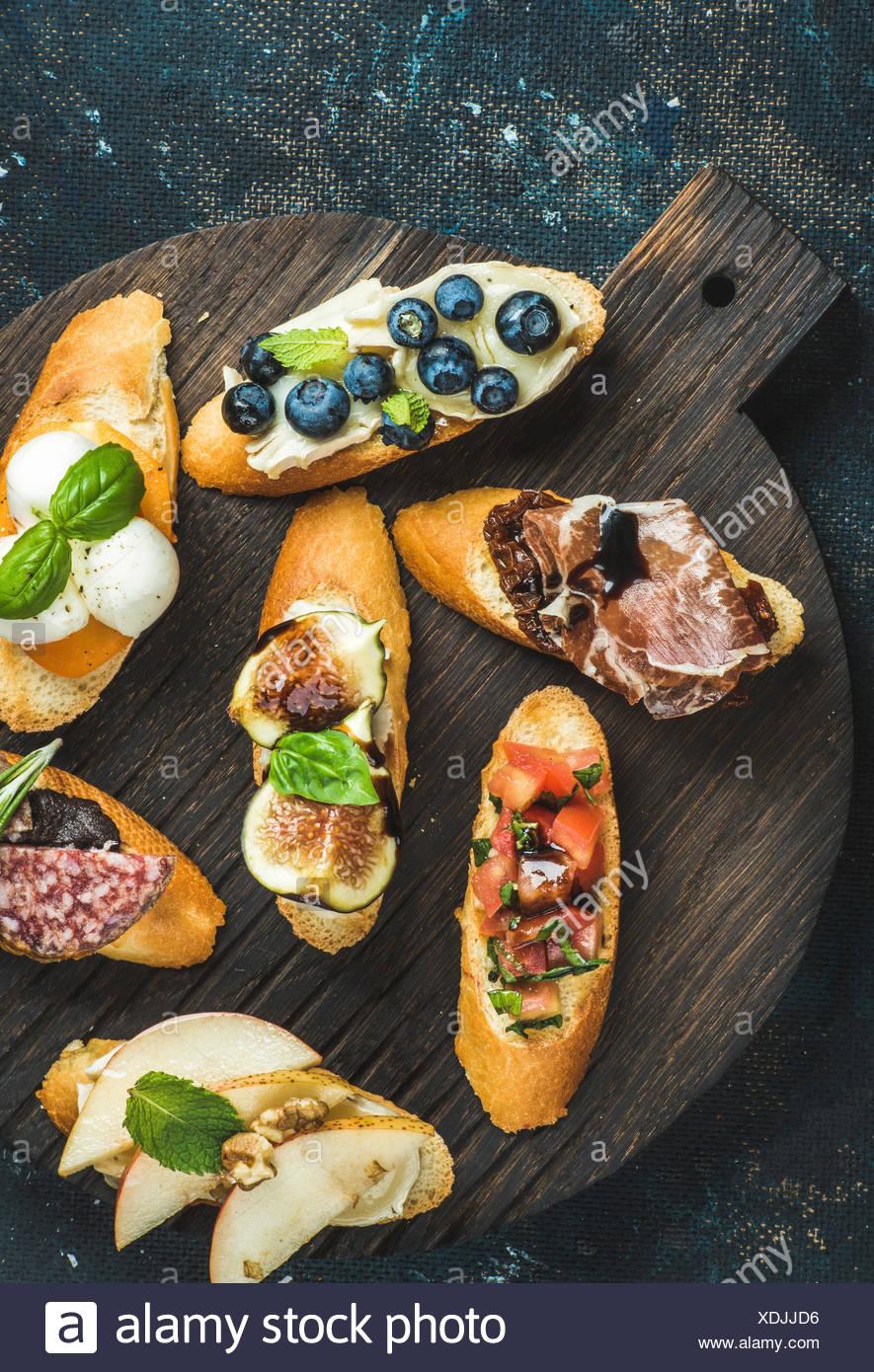 Crostini italiano con vari ingredienti sulla rotonda che serve in legno bordo nero su sfondo di legno compensato, vista dall'alto Immagini Stock