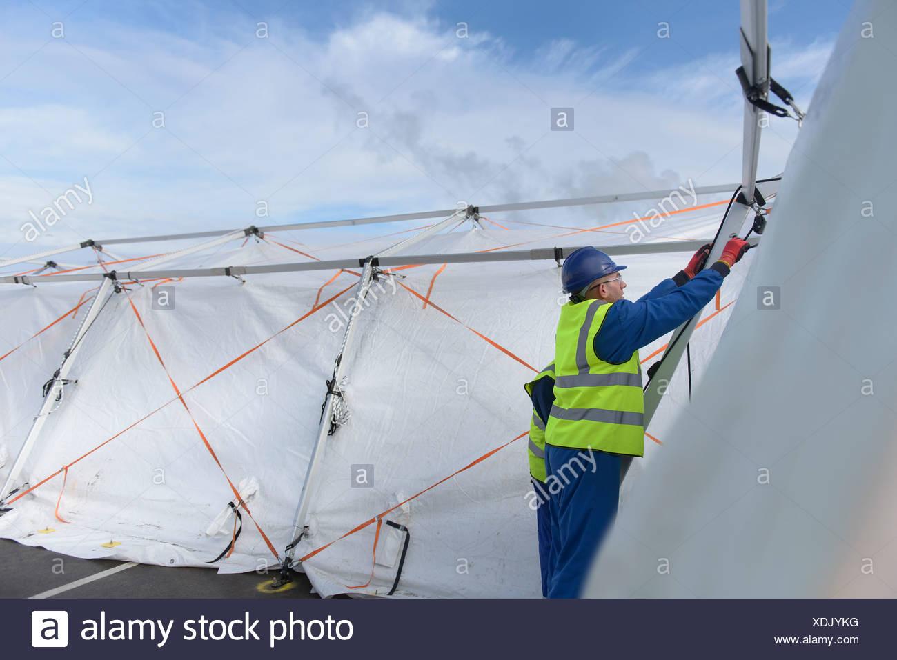 Il team di risposta alle emergenze lavoratori erigere tenda centro di controllo Immagini Stock