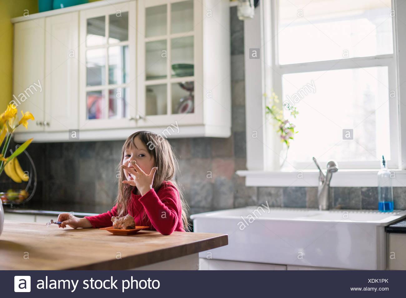 Ragazza seduta in cucina mangiare il cioccolato dolce e leccarsi le dita Immagini Stock