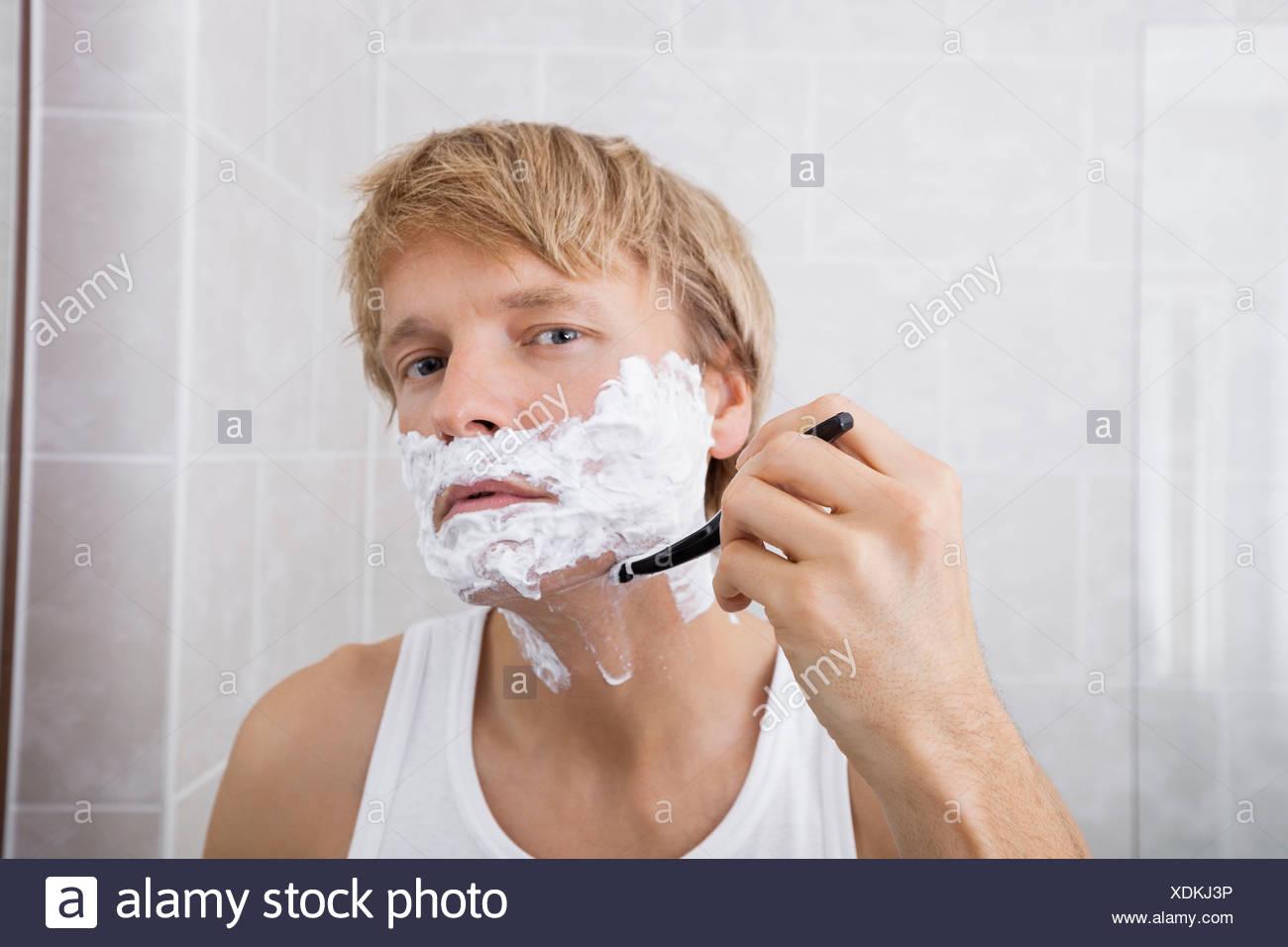 Ritratto di metà di uomo adulto la rasatura in bagno Immagini Stock