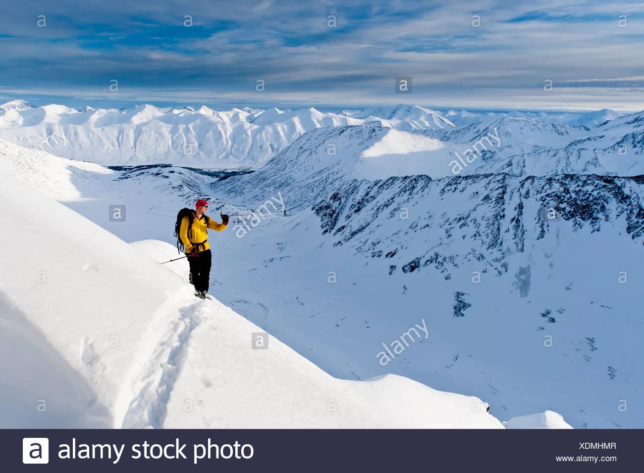 Sciatore sale elevato per gli sci il ripido fronte sud-ovest del monte Kickstep, Turnagain Pass, Kenai Mountains in Alaska centromeridionale Foto Stock