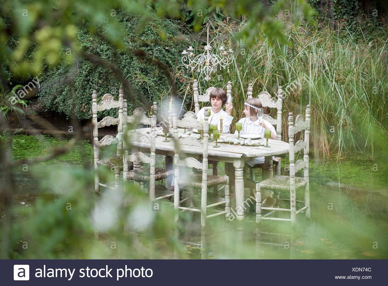 I bambini seduti al tavolo da pranzo galleggiante sul lago Immagini Stock