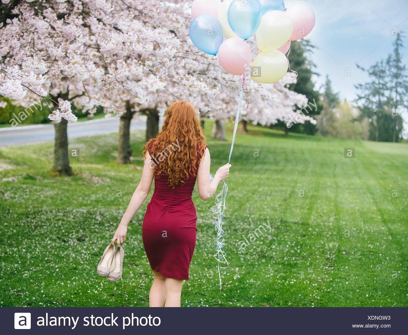 Vista posteriore della giovane donna con ondulata lungo i capelli rossi e il mazzetto di palloncini passeggiando nel Parco di primavera Immagini Stock