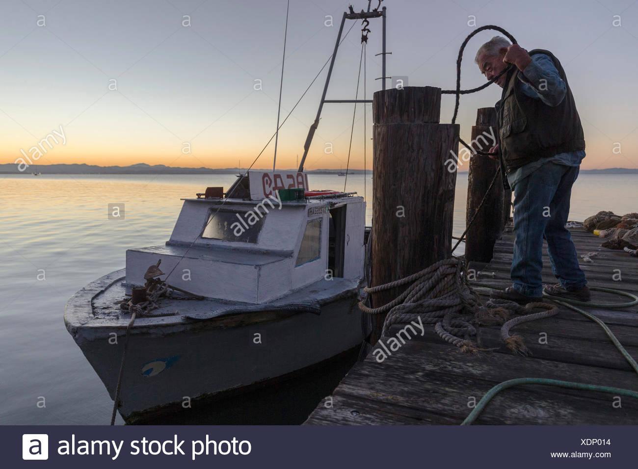 Pescatore di gamberetti in piedi sul molo vicino a barca al tramonto,Cina camp,California , Stati Uniti Immagini Stock