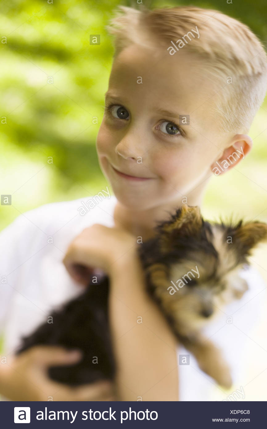 Ragazzo tenendo un cane di piccola taglia Immagini Stock