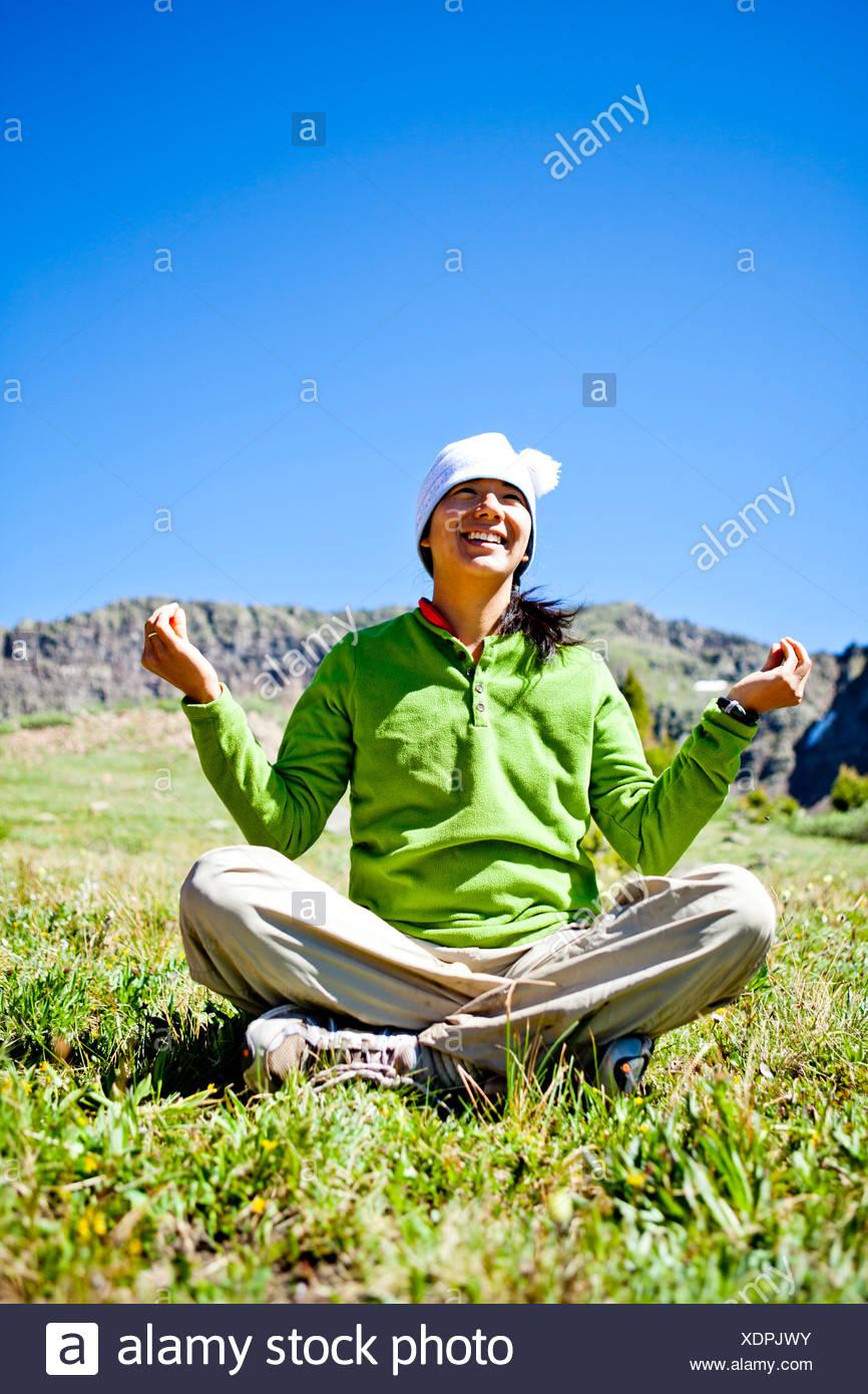 Una donna sorrisi come siede zampe trasversale in un prato con fiori selvaggi facendo un Buddha pongono. Sono appena fuori la Continen Immagini Stock