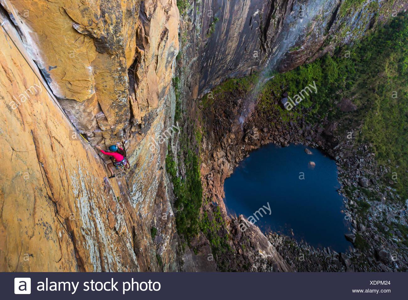 Una donna salendo accanto ad una cascata in una parete rocciosa. Immagini Stock