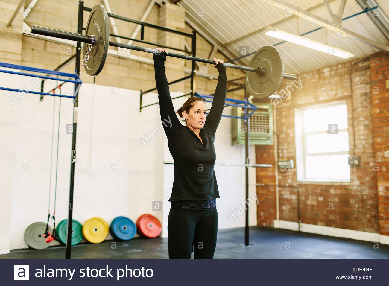 Sollevamento donna barbell in palestra Foto Stock