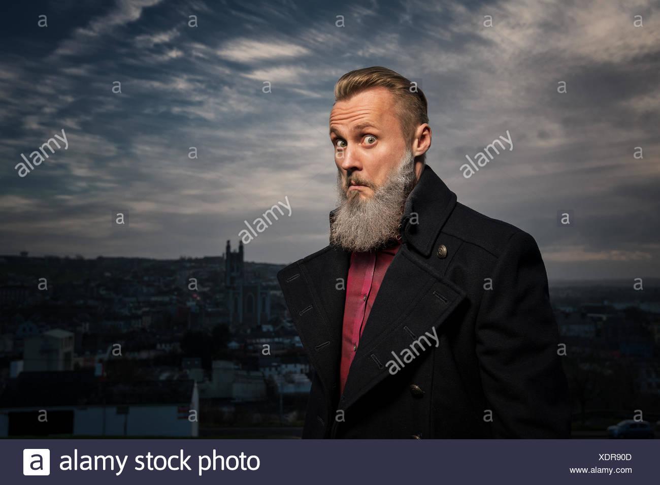 Hipster uomo rendendo divertente volto Foto Stock