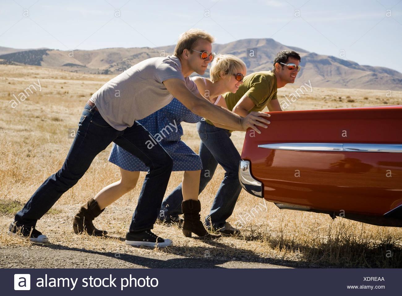 Persone spingendo un auto lungo la strada Immagini Stock