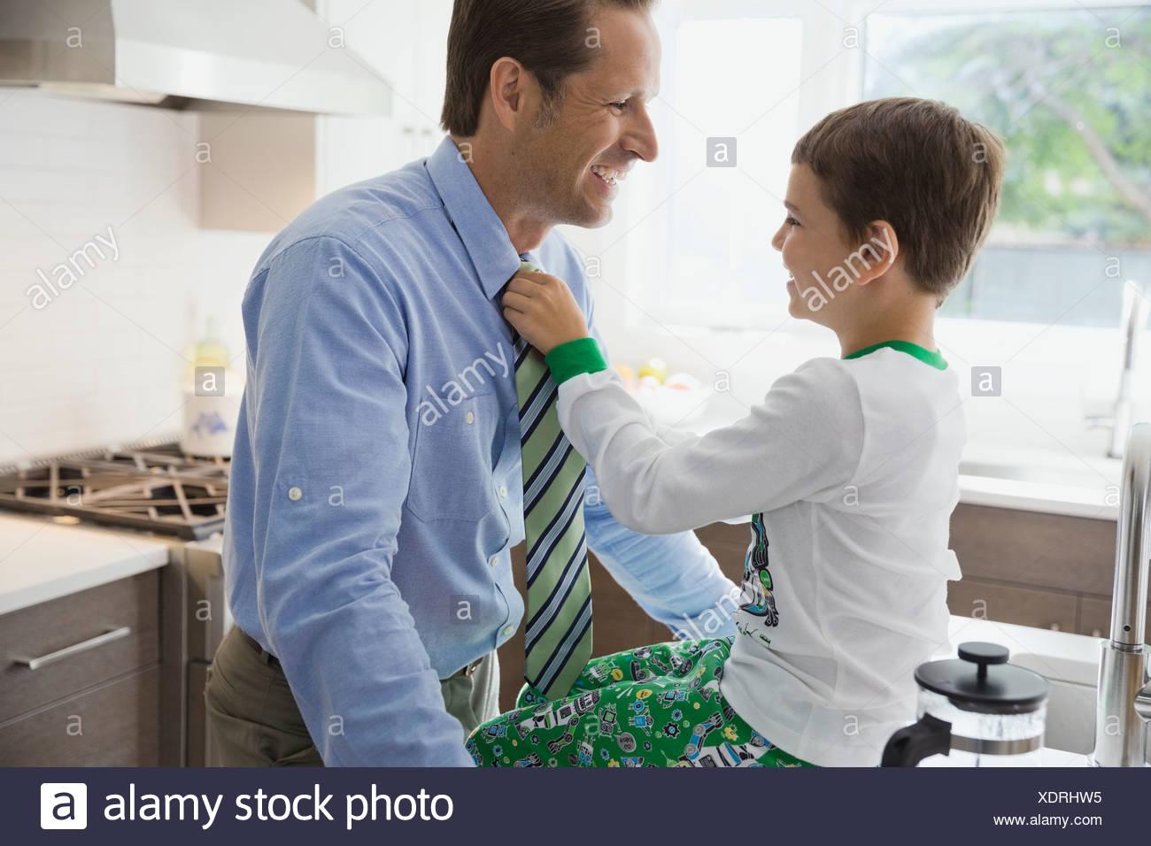 Figlio padri di regolazione cravatta in cucina Immagini Stock