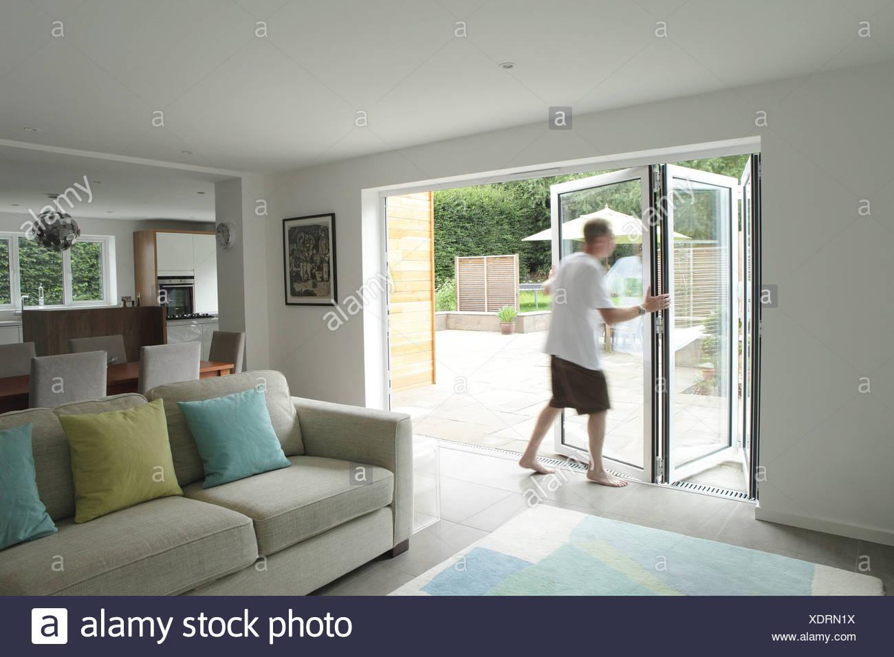 Uomo di aprire le porte del patio in zona soggiorno Immagini Stock