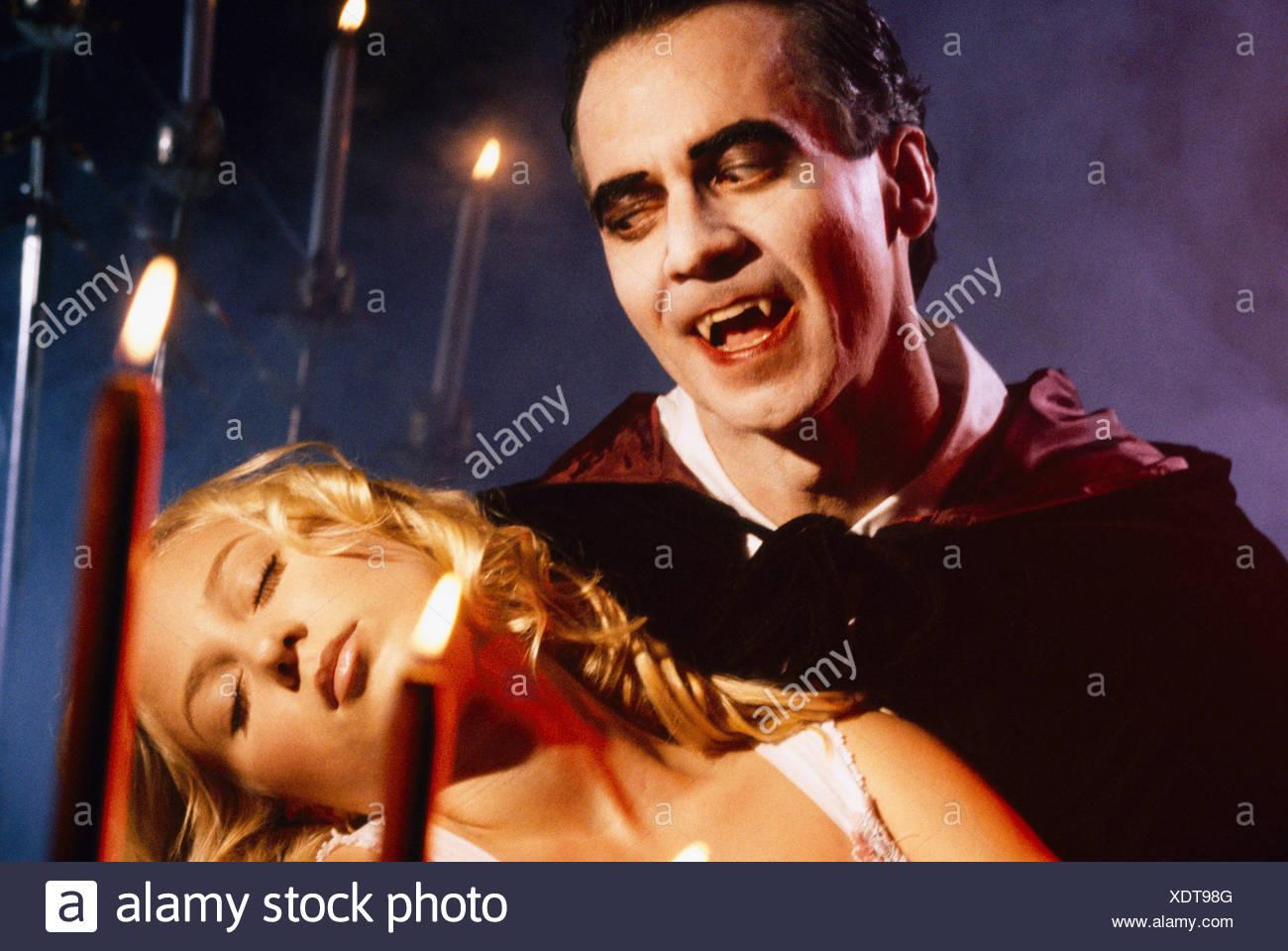 Close-up di un vampiro che trasportano un inconscio giovane donna Immagini Stock