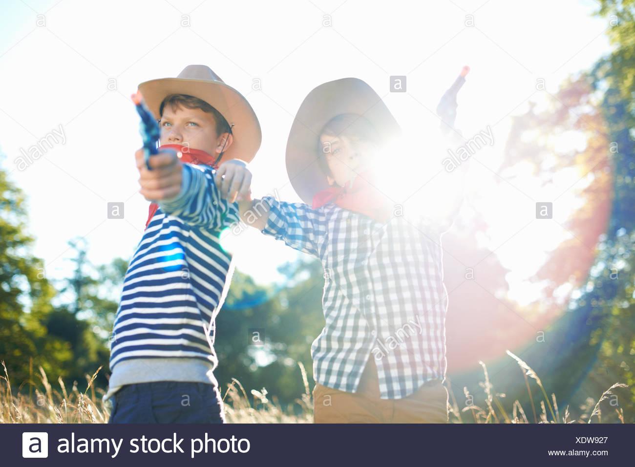 Due giovani ragazzi vestito da cowboy, tenendo pistole giocattolo Immagini Stock