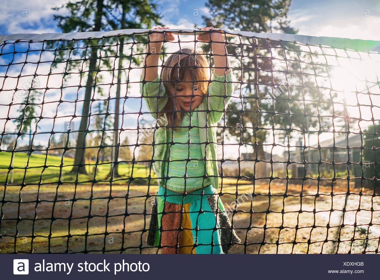 Ragazza in piedi sul campo da tennis net di sollevamento Foto Stock