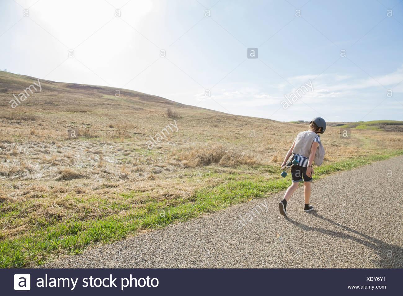 Vista posteriore della ragazza camminare sulla strada con lo skateboard Immagini Stock