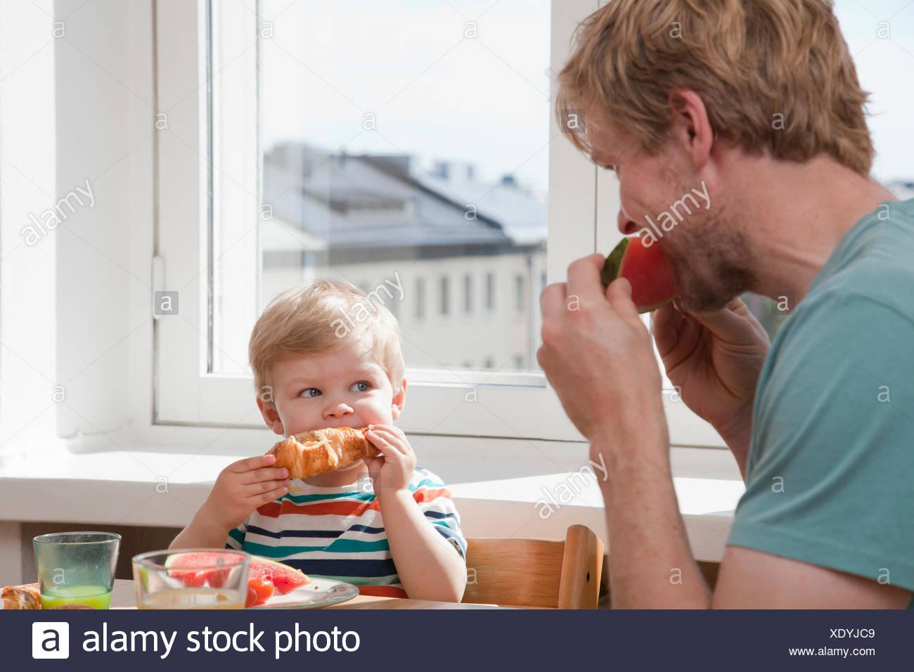 Padre e figlio dei bimbi di mangiare la prima colazione al tavolo della cucina Immagini Stock