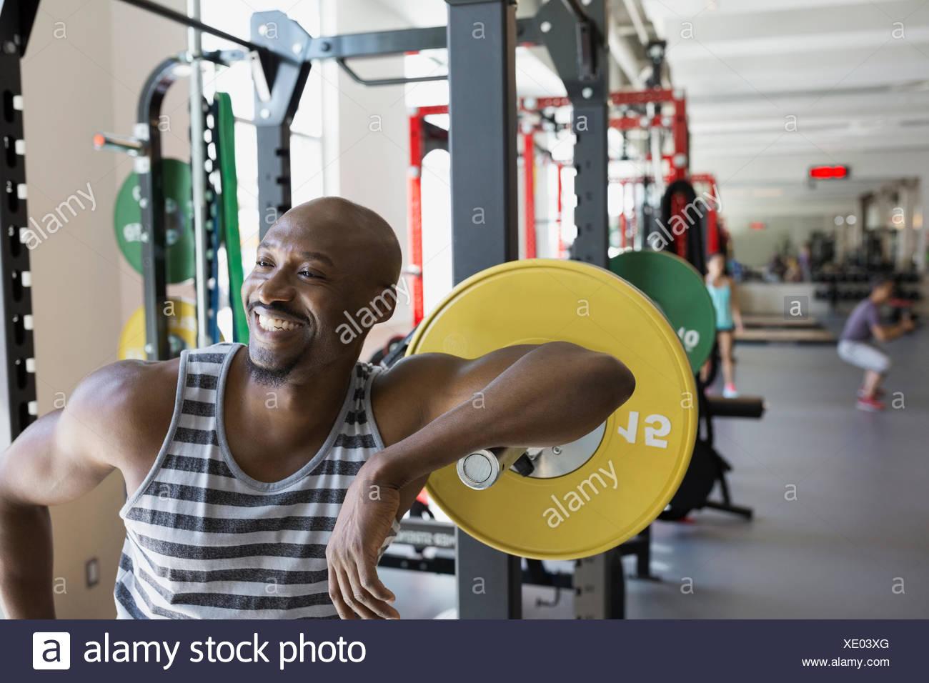 Entusiastico uomo appoggiato su barbell in palestra Foto Stock