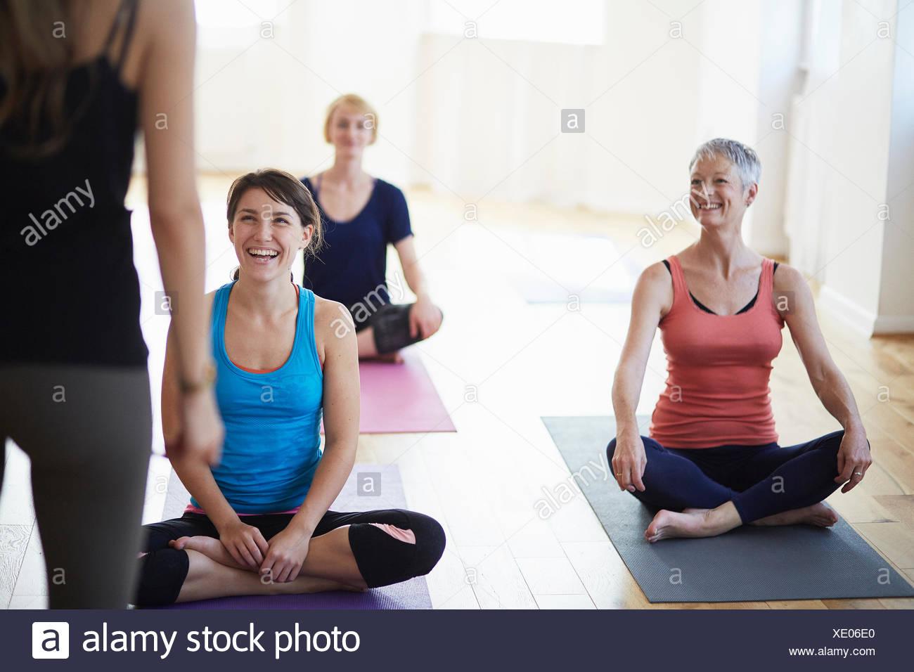 Studenti di sesso femminile guardando e ascoltando il tutor di classe di pilates Immagini Stock