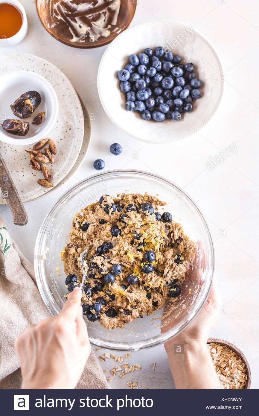 I mirtilli vengono miscelati in pasta per colazione scones. Immagini Stock