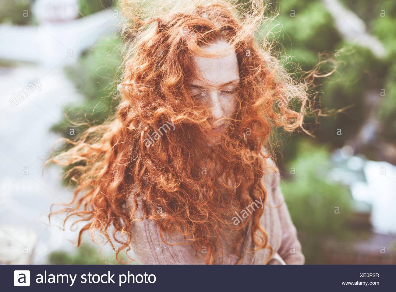 Ritratto di giovane donna con lunghi, ricci capelli rossi Immagini Stock