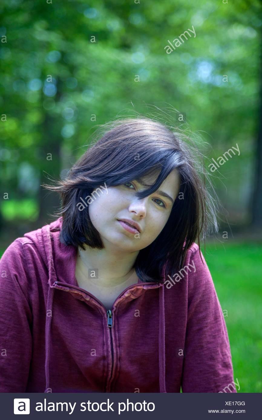Giovane donna, che indossa una felpa rossa nella parte anteriore degli alberi in un parco. Immagini Stock