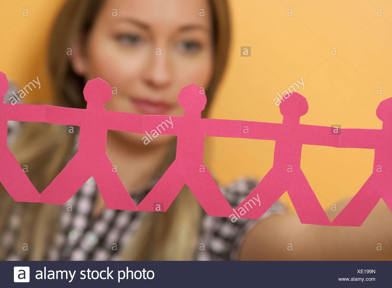 Una donna è in possesso di una catena di figure intagliate di carta Immagini Stock