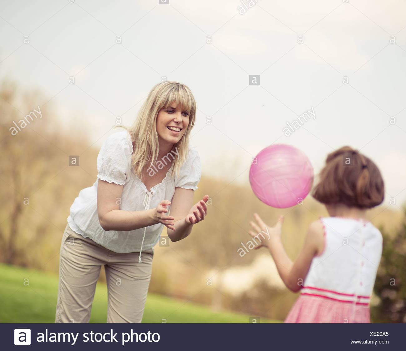Famiglia lanciando la palla a vicenda nel parco Foto Stock