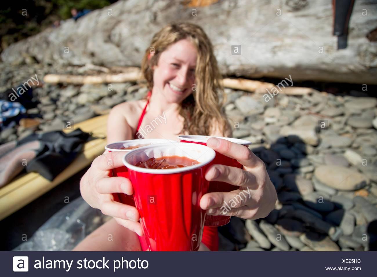 Giovane donna seduta sulla spiaggia rocciosa, tenendo le bevande, sorridente, breve Sands Beach, Oregon, Stati Uniti d'America Immagini Stock