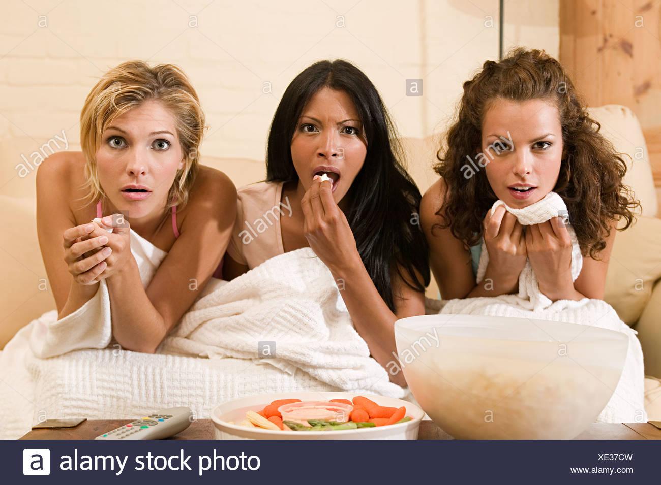 Gli amici a guardare un film horror Immagini Stock
