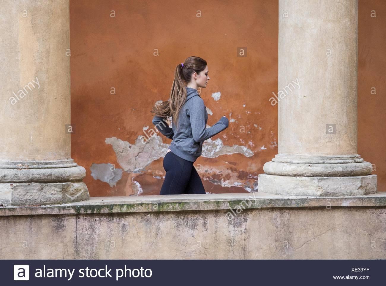 Giovane donna che indossa abiti sportivi jogging Immagini Stock