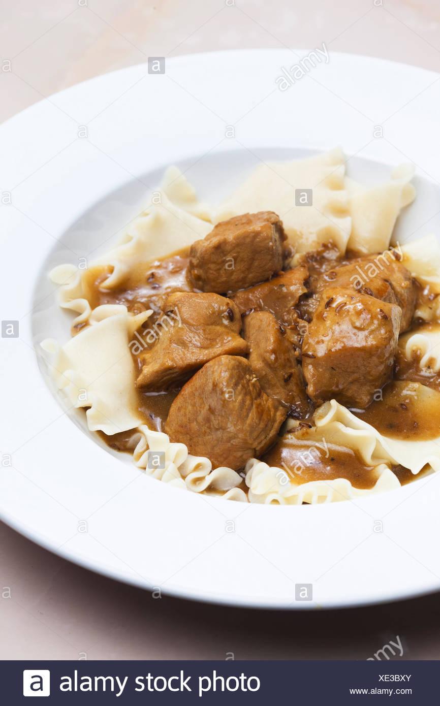 Pezzi di carne di maiale sul cumino con la pasta. Immagini Stock