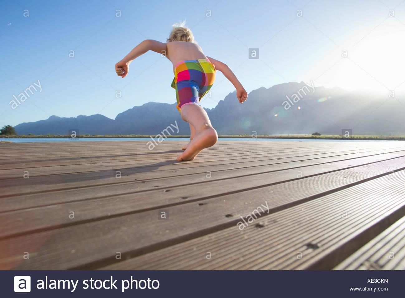 Ragazzo in esecuzione a saltare in un lago da un pontile Immagini Stock