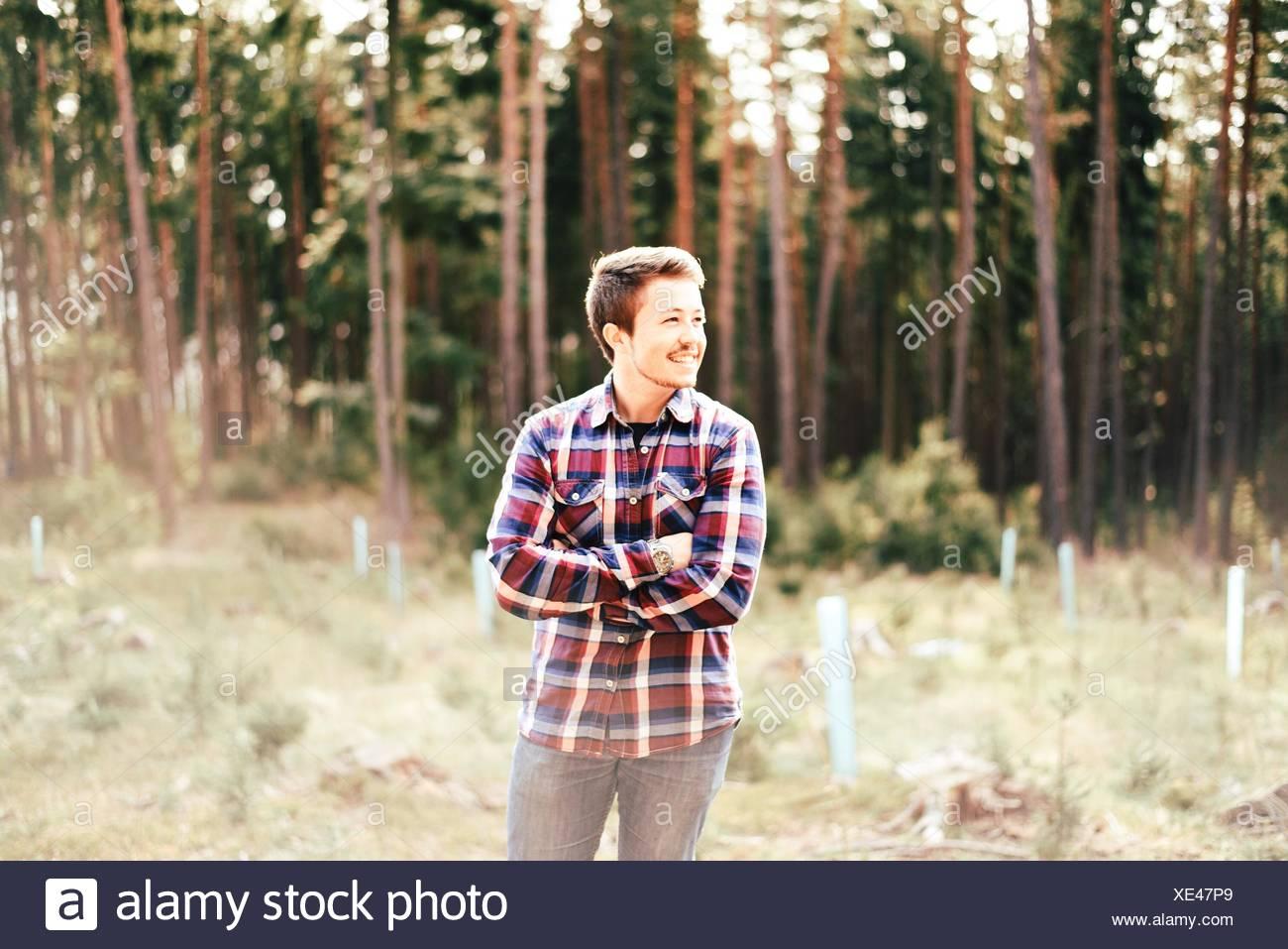 Felice l'uomo in piedi con le braccia incrociate nella foresta Immagini Stock