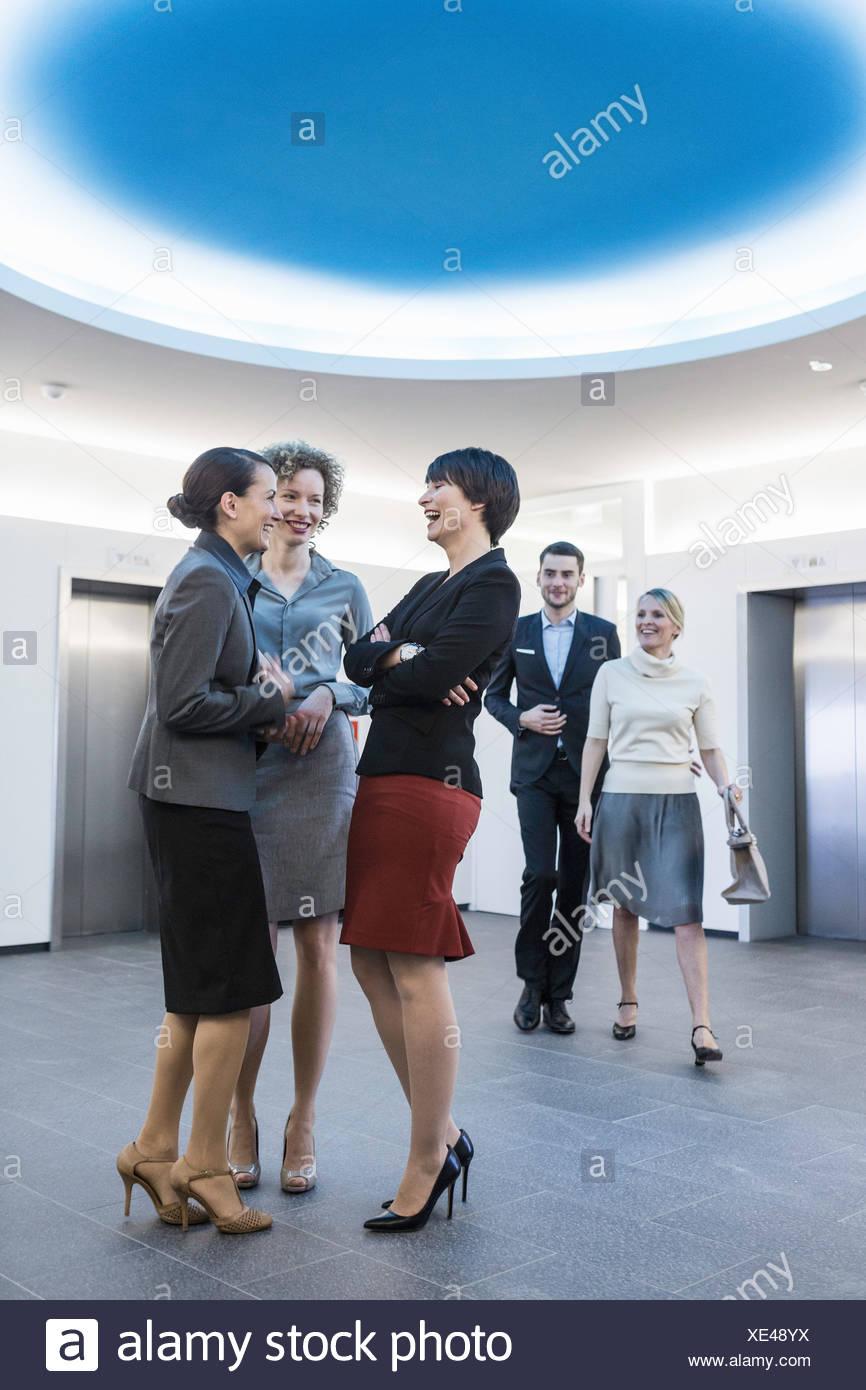 Gli imprenditori aventi la conversazione in atrium Immagini Stock