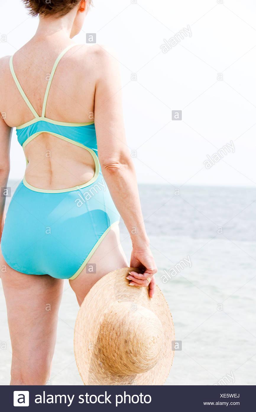 25286e2bdab9 Tagliate il ritratto di una donna senior in un costume da bagno in spiaggia  tenendo un cappello di paglia