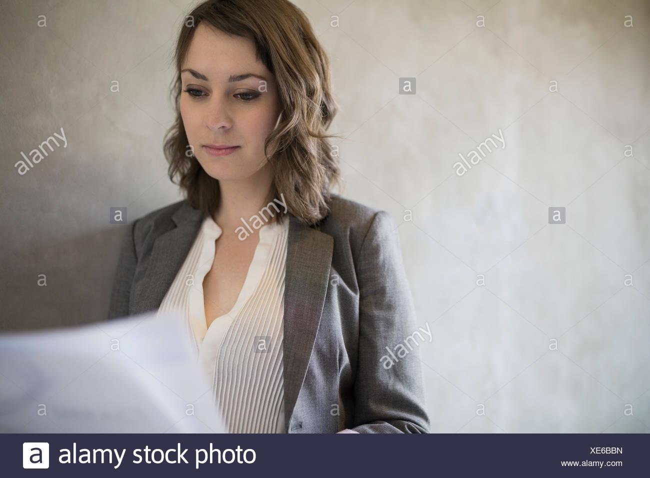 Focalizzato brunette imprenditrice la lettura di documenti cartacei Immagini Stock
