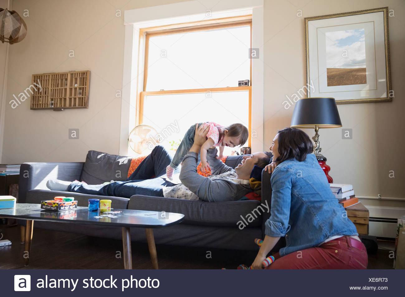 Famiglia giovane rilassante nella stanza vivente Immagini Stock