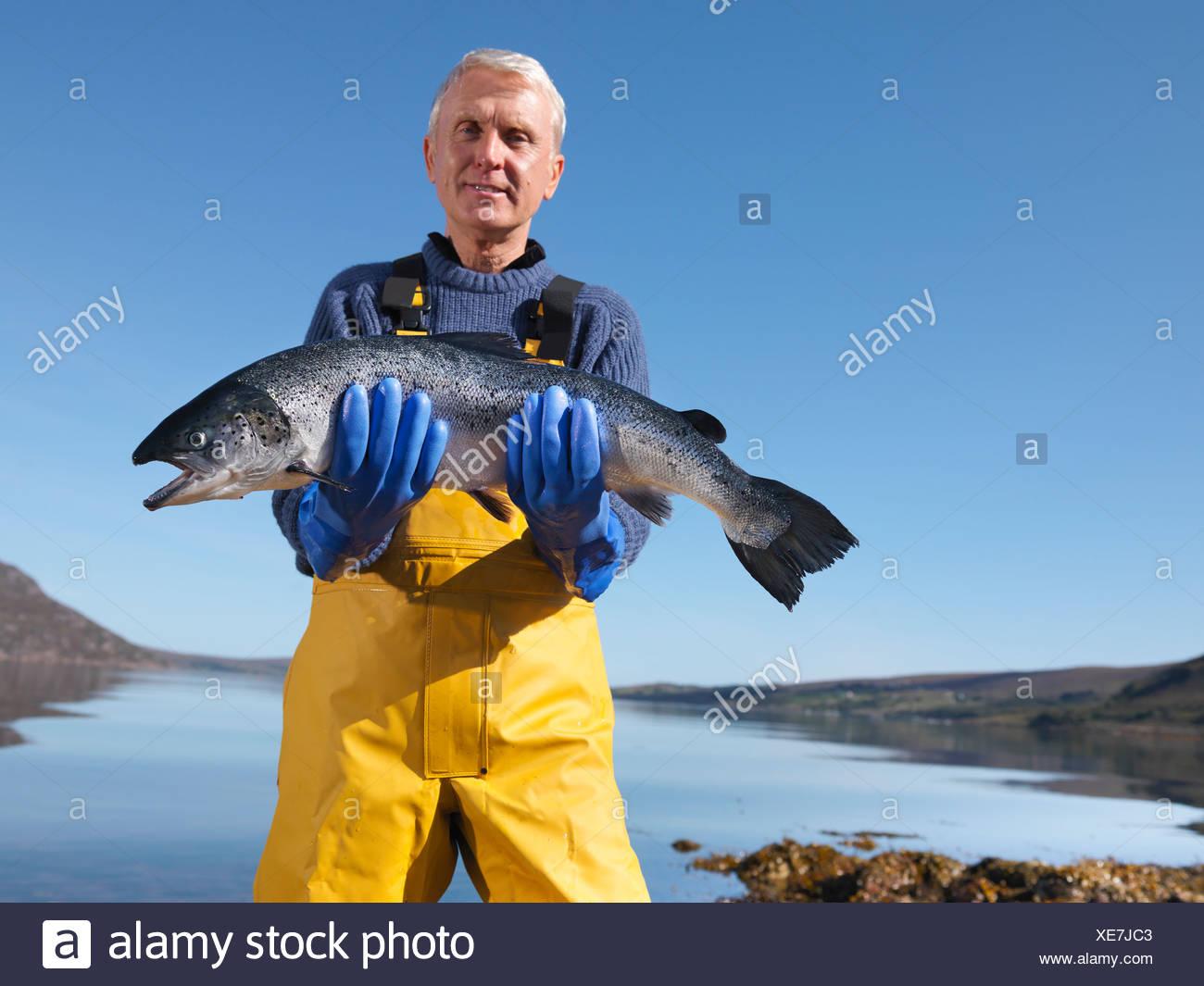 Fisherman tenendo il salmone dal lago Immagini Stock