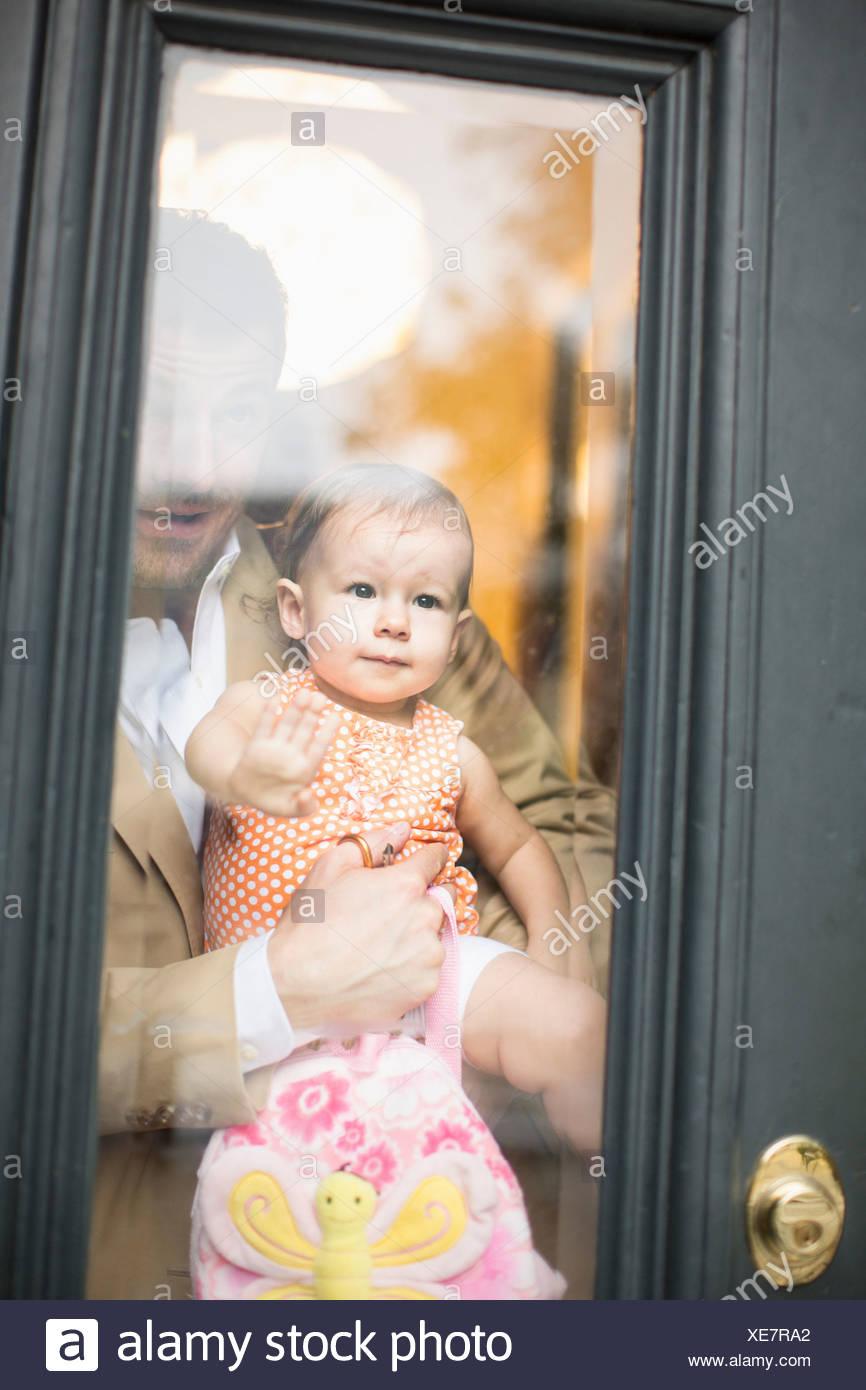 Uomo con bambino guardando attraverso lo sportello anteriore Immagini Stock