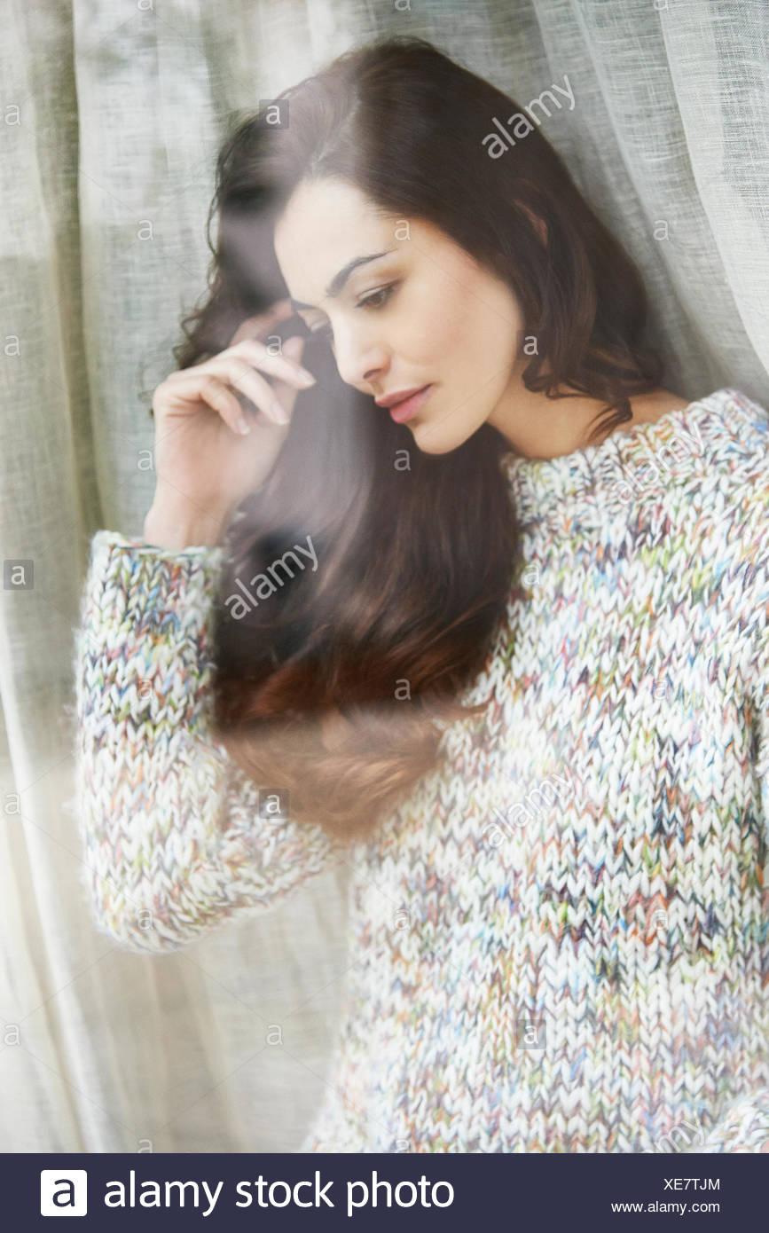 Donna in piedi da una finestra Immagini Stock