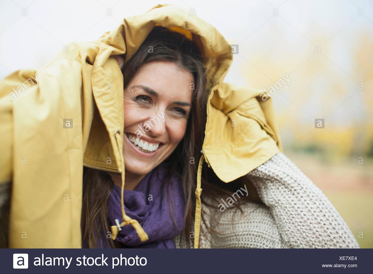 Donna matura con giacca sopra la testa Immagini Stock