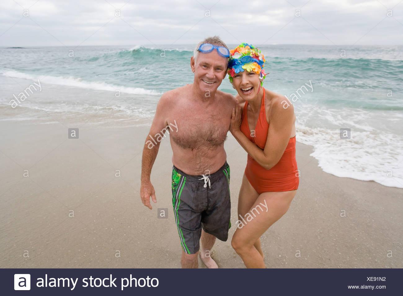 d2cfe528ecd1 Coppia matura in costume da bagno a braccetto sulla spiaggia, sorridente,  ritratto